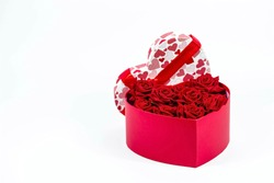 Valentine's Day. Red roses in a white box in the form of a heart on a white background. A gift for women on a holiday. The concept of delivering flowers. floristry and flower shops. Copy space.