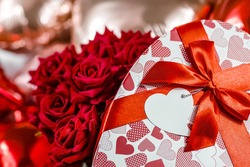 Valentine's day. Red roses in a white box in the form of a heart on the background of foil balls. A gift for women on a holiday. The concept of delivering flowers. floristry and flower shops.