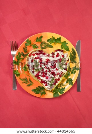 Valentine's day salad with beef tongue, onion and apple in heart shape on red table-cloth decorated with greens and  pomegranate seeds
