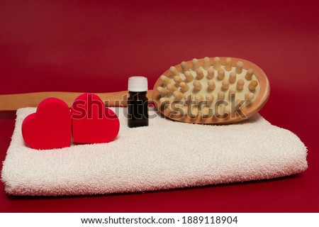 valentine's day spa. two red hearts on a white towel, a jar of essential oil and a massage brush in the background, partially out of focus. red background Stock fotó ©
