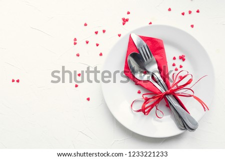 Valentine's Day tabble setting with cutlery on white background. Romantic dinner concept. Valentine day or proposal background. Mockup design layout for your text. Copy space. Top view.