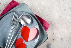 Valentine's Day Table Setting. Plate with cutlery, red hearts. Flat lay, top view, copy space