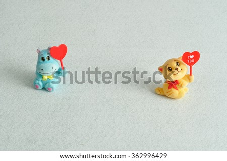 Valentine's day. Two figurines holding hearts #362996429