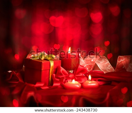 Valentine\'s Day. Valentine Red Heart shaped candles and Gift on Red Silk over glowing background. Beautiful Valentine card art design
