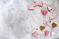Valentine's day with a hearts, cookies in the shape of a heart, Icing, Red ribbon on Vintage gray texture table Top View Copy Space Gingerbread painting Horizontal Postcard