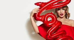 Valentine's Day. Word love letters from the inflatable. Girl holding a big word love.Girl with retro hairstyle in red dress in studio on a white background.