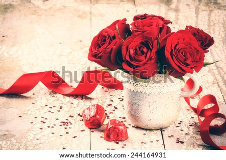 Valentine\'s setting with bouquet of red roses and chocolate
