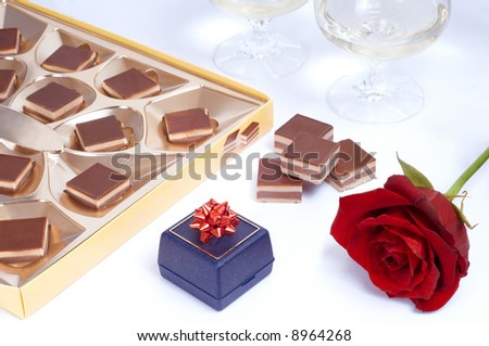 Valentine table with rose, box of chocolates, gift box and two glasses of white wine on white background.