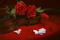 Valentine violin, red roses on dark red silk sheet, romantic instrument for valentine's day celebration