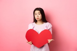 Valentines concept. Single teenage asian girl wants to fall in love, looking sad and lonely at camera, sulking distressed on lovers day, holding big red heart cutout, pink background
