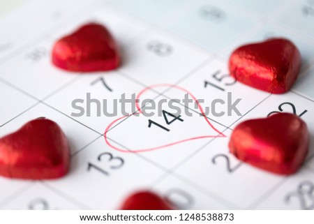valentines day and holidays concept - close up of calendar sheet with marked 14th february date and red heart shaped chocolate candies #1248538873