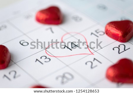 valentines day and holidays concept - close up of calendar sheet with marked 14th february date and red heart shaped chocolate candies #1254128653