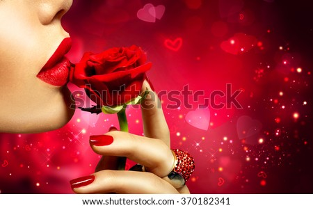 Valentines Day art design. Beautiful Model woman kissing red rose flower. Red Lips, Nails and Rose. Beauty Girl. Makeup and Manicure. Sensual Mouth. Sexy Red Color Lips. St. Valentine\'s Day design
