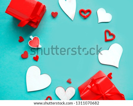 Valentines Day background. Hand made wooden hearts and red gift boxes on blue background. Flat lay, top view, copy space #1311070682