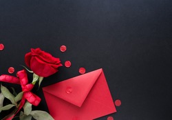 Valentines day background. Red flowers of rose and envelop on black background, top view, copy space