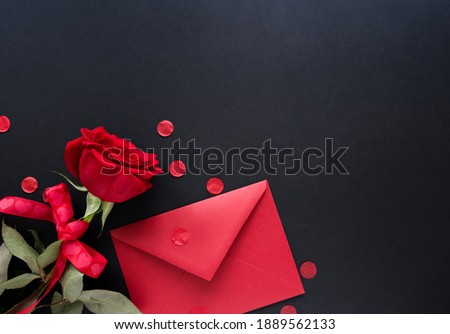 Photo of  Valentines day background. Red flowers of rose and envelop on black background, top view, copy space