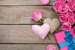 Valentines day background with gift box full of pink roses and handmaded toy hearts over wooden table. Top view with copy space