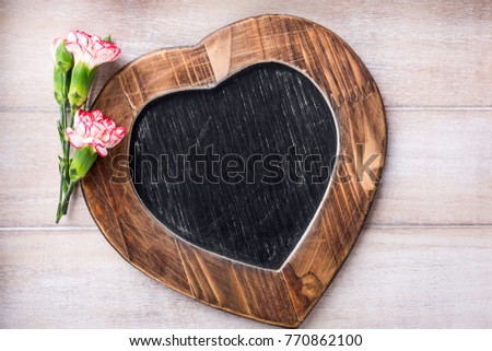 Valentines Day background with vintage slate chalk board in heart form and pink carnation flowers with copy space for text. View from above. #770862100