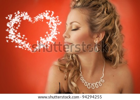 Valentines Day. Beautiful woman girl dreaming of love in Valentines Day with heart sign with copy space on red background closeup isolated in studio - stock photo
