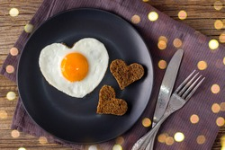 Valentines day breakfast with heart shaped fried eggs served on grey plate and napkin. flat lay, top view with bokeh