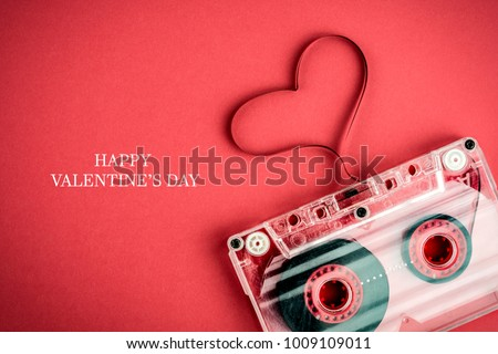 Valentines day card, audio cassette with magnetic tape in shape of heart on red background