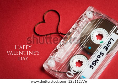 Valentines day card - audio cassette with magnetic tape in shape of heart on red background