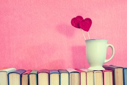Valentines day concept. Cup with crochet hearts on books over pink background.