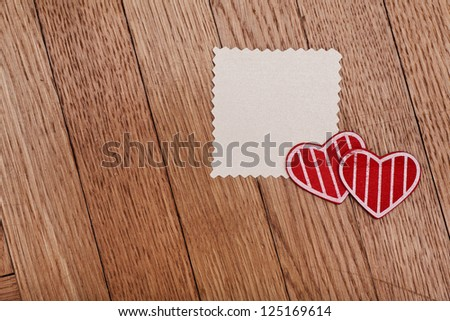 valentines day concept: empty paper and two red hearts