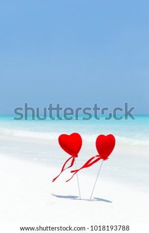 Valentines day concept greeting card, two red hearts on pristine sandy beach, honeymoon vacation background