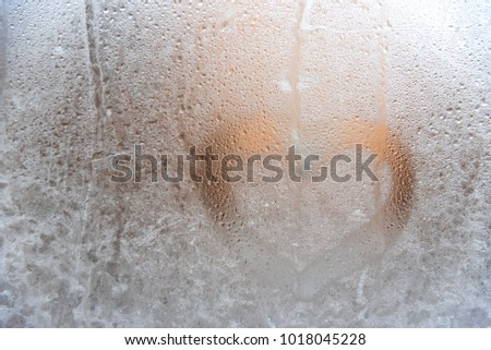 Valentines day concept heart shape written on a frosty window and a frosty glass. Winter cold, frosty window.