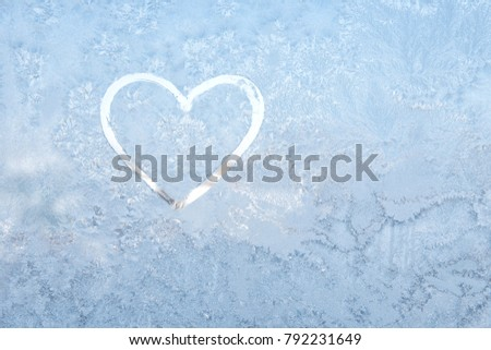 Valentines day concept heart shape written on a frosty window and a frosty glass. Winter cold, frosty window, the inscription on the frosty glass heart