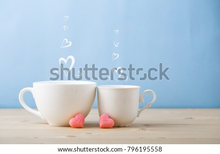 Valentines day concept, mugs cups of coffee or tea for two lovers honeymoon wedding morning surprise breakfast, pink heart sugar candies, blue background pastel colors copy space, light wooden table