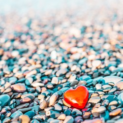 Valentines Day concept. Romantic love symbol of red heart on the pebble beach with copy space. Template for Inspirational compositions and quote postcards.