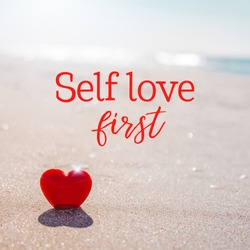 Valentines Day concept. Romantic love symbol of red heart on the sand beach with copy space and text message. Inspirational quote postcard. Self discovery, self growth, personal development concept