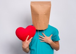 Valentines Day concept. Teen boy with paper bag over head holds red heart. Boy holding symbol of love, family, hope. Teenager cover head with bag posing in studio. Child pulling paper bag over head.