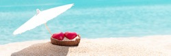 Valentines day concept. Two hearts - symbol of love couple on sand paradise tropical beach under parasol. Blue sea and sky in background. Love, togetherness, marriage. Traveling together. Wide banner
