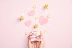 Valentines day gift box in female hands, paper hearts, flowers and decorations on pink background. Flat lay, top view.