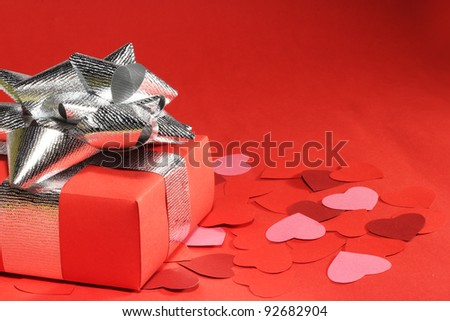 Valentines Day gift in box and small hearts on red background