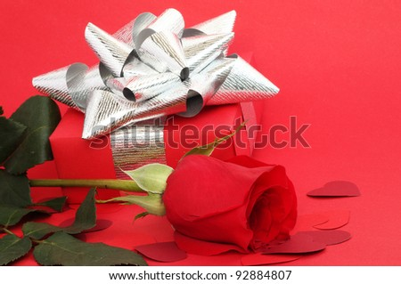 Valentines Day gift in box with rose and small hearts on red background