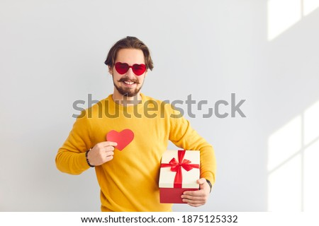 Photo of  Valentines Day gift. Portrait of a cheerful man in festive glasses holding a gift and a heart as a symbol of love for his beloved. Hipster posing on a wall background. Concept of love and romance.