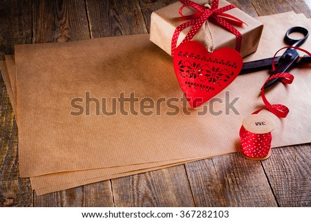Valentines day gift wrapping with boxes and scissors over paper or wooden background.