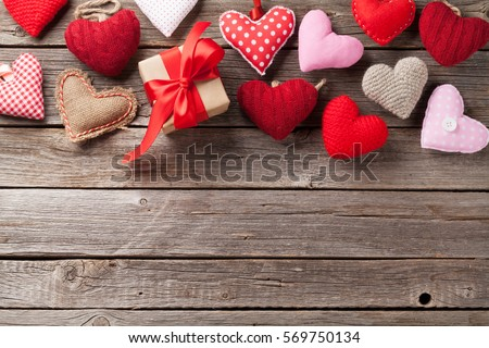 Valentines day greeting card. Handmaded hearts and gift box on wooden table. Top view with copy space