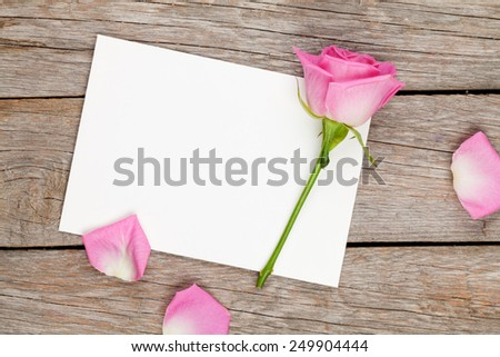 Valentines day greeting card or photo frame and pink rose over wooden table. Top view with copy space