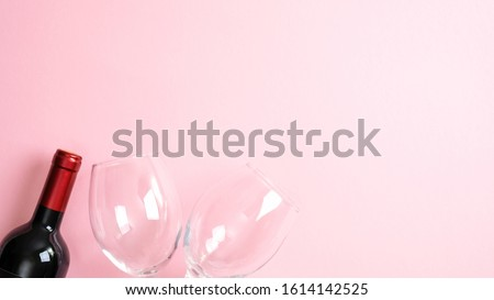 Valentines day greeting card template. Bottle of wine and glasses on pink background. Top view with copy space. Valentine's day, love, romance concept