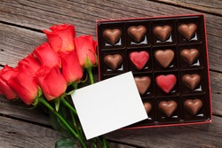 Valentines day greeting card with red roses and heart chocolate box on wooden table. Top view with space for your greetings