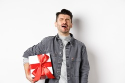Valentines day heartbreak. Single and heartbroken guy crying lonely, holding big gift box, being rejected by lover, sobbing and feeling alone, standing on white background