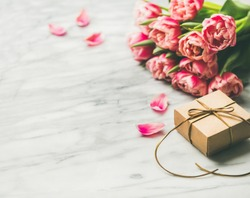 Valentines day holiday background. Bouquet of pink tulips and gift box with ribbon over white marble table background. Pink tulips and gift box with copy space. Lovers or Womens day greeting card