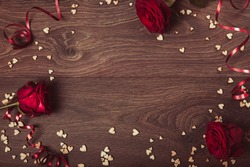 Valentines day holiday composition, ornament. Festive creative pattern, red roses, hearts and ribbon on wooden brown background. Flat lay, top view. Birthday, Mother's, Women's, Wedding Day concept.