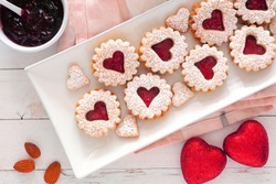 Valentines Day jam cookies with heart shapes. Above view on a serving plate against a white wood background