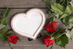 Valentines Day. Love heart photo frame and red roses on the wooden background, top view. Love, romantic and Valentine's concept. Copy space in photo frame for insert love message or photo